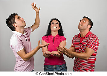 Group of three people catching something - Group of three...