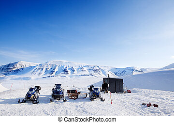 Winter Base Camp - People preparing snowmobiles for an...