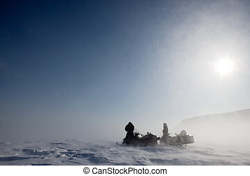 Blizzard - A pair of snowmobiles in a winter blizzard with...