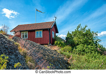 Summer in Sweden - Traditional red little cottage on...