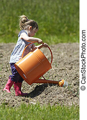 Stock photo of a child with a watering can - A little girl...