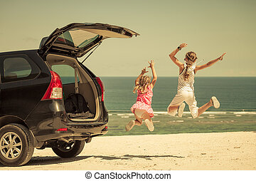two sisters standing near a car on the beach