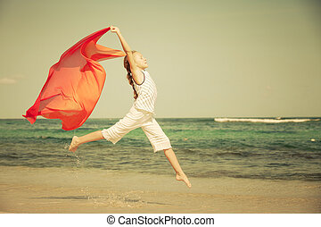 teen girl jumping on the beach at blue sea shore in summer...