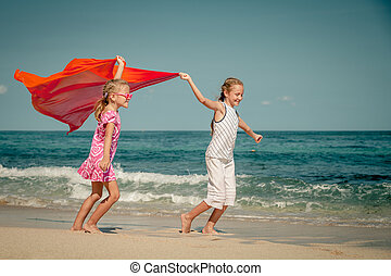 two sisters standing on the beach and pulled up his hands