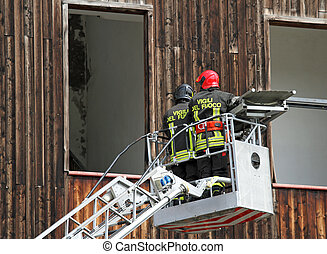 Italian firefighters while rising with the mobile platform...