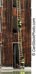 firefighters with ladder during a practice session in the...