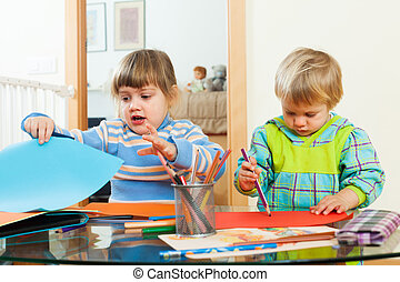 serious children playing with paper and pencils in home...