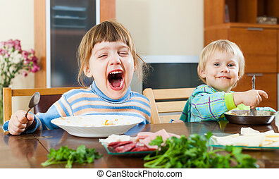 baby girls eating food at table - happy emotional baby girls...