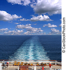 Cruise ship track on the ocean with clouds in the background