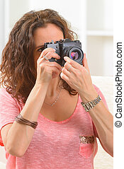Mature woman taking pictures with old analog SLR camera at...
