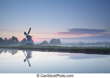 windmill by river at sunrise