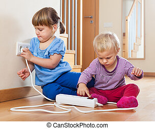 children playing with electrical extension and outlet - Two...