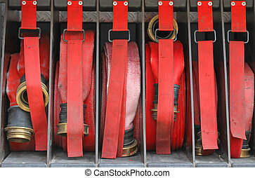 Six red hoses of firefighters in order inside the fire truck