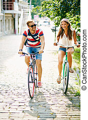 Cycling in the park - Portrait of happy girl and guy cycling...