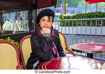 Teenager sitting at a table cafe on the Champs Elysees,...
