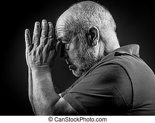 Old man praying with his hands joined black and white...