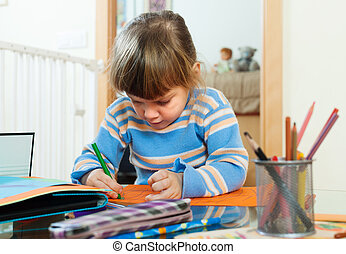serious child drawing on paper in home