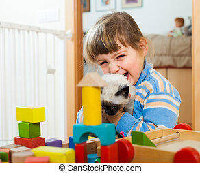 Happy 3 years child playing with kitten in home interior
