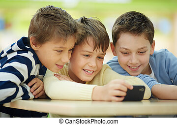 Children with smartphone - Three boys surfing the net on...