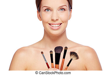 Cosmetologist - Portrait of young female with beauty tools...