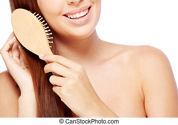 Hair care - Close-up of young woman brushing her long hair
