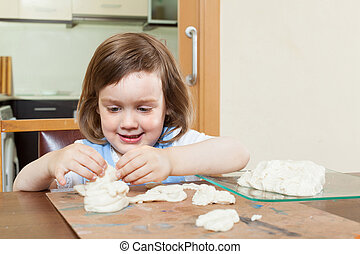 Cute little girl making dough figurines in the room