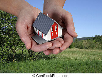 House on hands in front of a green landscape.