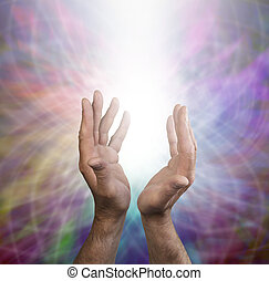 Male healing hands outstretched beaming white energy on a...