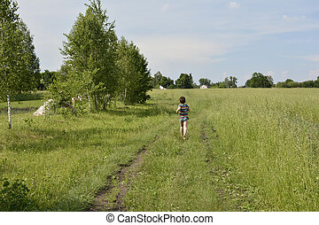 A village boy runs down the road in the field.