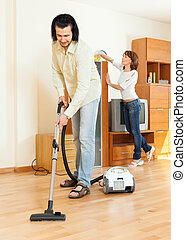couple cleaning with vacuum cleaner in home - middle-aged...