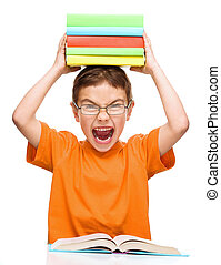 Little boy is holding a pile of books and showing aggressive...