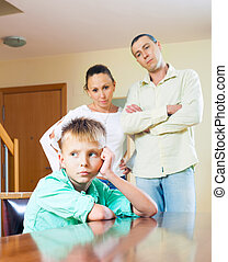 Parents scolding teenage child in home interior Focus on boy...