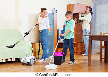 family of three with teenager doing housework with cleaning...