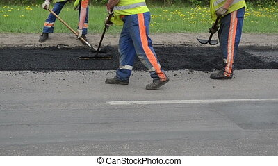 level asphalt road repair - Workers with shovels and special...