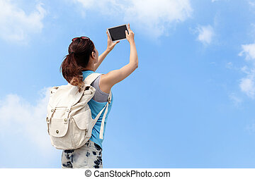 Happy woman traveler photo by tablet pc with blue sky