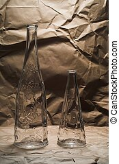 Two bottles on cardboard with a crushed paper background