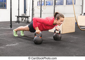 Young woman trains pushups with kettlebells - Young hard...