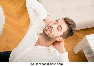 Relaxed - A young adult man relaxing and stretching his back...