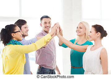 creative team doing high five gesture in office - business,...