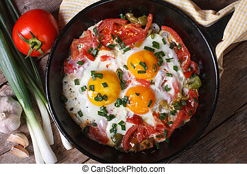 Fried eggs with vegetables on a pan and the ingredients -...