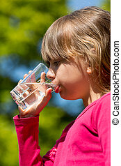 Girl drinking water - Young caucasian girl drinking from...
