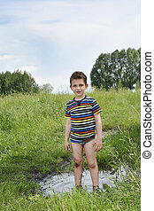Dirty rural boy stands barefoot in a puddle.