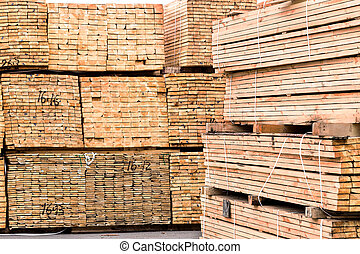 A pile of wood edged boards packed in stacks with tags size para
