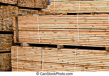 A pile of wood edged boards packed in stacks with tags size...