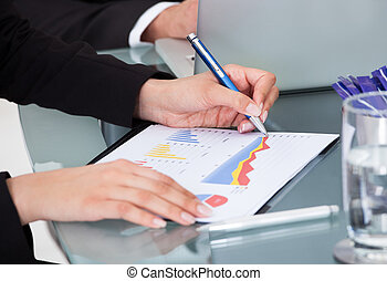 Businesswoman Writing On Graph - Cropped image of...