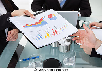 Businesswoman Giving Progress Chart To Colleague