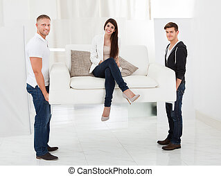 Movers Carrying Sofa With Client - Full length portrait of...