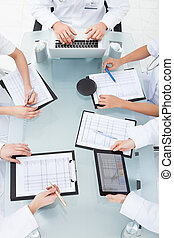 Doctors Examining Medical Reports - Cropped image of doctors...