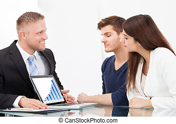 Advisor Showing Investment Plans To Couple On Laptop - Male...