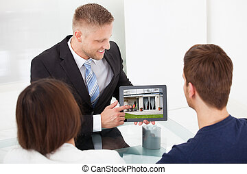Advisor Showing House Picture To Couple On Tablet - Smiling...